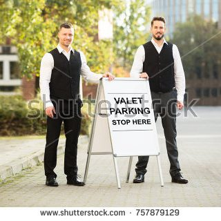 stock-photo-portrait-of-a-smiling-young-male-valet-standing-near-valet-parking-sign-757879129